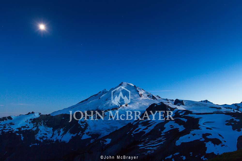 The moon sits above Mt Baker as the last bit of daylight slips away. © John McBrayer