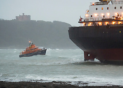 © Licensed to London News Pictures. 18/12/2018. Falmouth, UK. A lifeboat circles as Russian cargo ship Kuzuma Minin, run aground on the reef off Gyllyngvase beach in Falmouth Bay in the early hours this morning. The Falmouth lifeboat and the Coastguard helicopter are involved in the major incident.  Photo credit: Mark Hemsworth/LNP