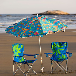 Beach chairs and an umbrella at Popham Beach State Park in Phippsburg, Maine.