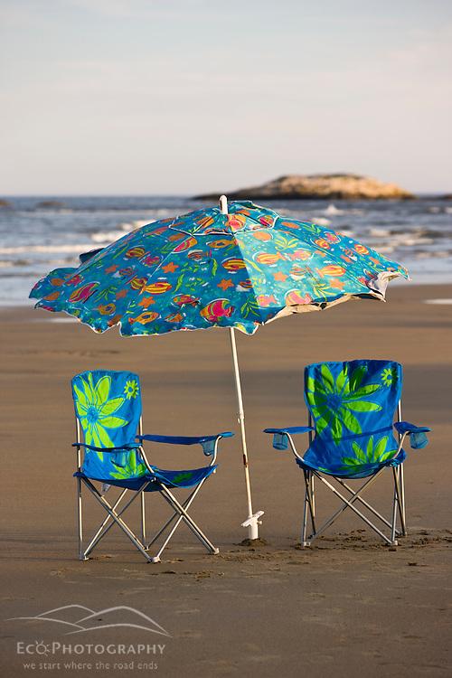 Beach chairs and an umbrella at Popham Beach State Park in Phippsburg, Maine.