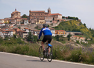 Woman riding bicycle up to hilltop village of La Morra in the Piedmont region of northern Italy. http://www.gettyimages.com/detail/photo/woman-riding-cycle-royalty-free-image/120297867