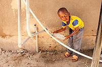 09 OCT 2009, DAR ES SALAAM/TANZANIA:<br /> Ein Junge zapft sich an einer undichten Wasserleitung etwas Wasser ab, auf einem Marktes, der durch ein Infrastruktur Projekt der DAWASA (Daressalam Water and Sanitation Authority) Water Systems einen Wassertank erhalten hat, ueber den zukuenftig die Marktstaende mit Wasser versorgen werden sollen, ONE Informationsreise nach Tansania<br /> IMAGE: 20091009-01-197<br /> KEYWORDS: Reise, Trip, Afrika, Africa, Gesundheit, Bildung, Wasserinfrastruktur, Wasserversorgung, Daressalam, Kind, Kinder, Trinkwasser