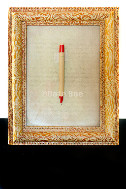 picture frame with pen taped on top of the glass