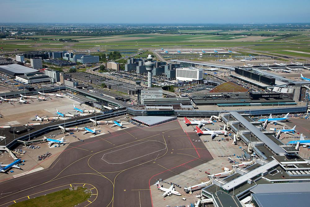 Nederland, Noord-Holland, Haarlemmermeer, 12-05-2009; stationsgebouw luchthaven Schiphol. In het midden de verkeertoren met vluchtleiding, en rechts hiervan vertrekhal en aankomsthal met en ingang Schiphol Plaza (overdekt winkelcentrum). Rechtsonder de D pier, linksonder de C pier. Aan de gates, geparkeerde vliegtuigen van onder andere Martinair en KLM. Op het tweede plan hotels  en diverse kantoorgebouwen geexploiteerd door Schiphol vastgoed (Schiphol Real Estate). Air view on Airport Schiphol, showing airplanes waiting to board and unboard, in the center the control tower. The airport is surrounded by offices. .Swart collectie, luchtfoto (toeslag); Swart Collection, aerial photo (additional fee required).foto Siebe Swart / photo Siebe Swart