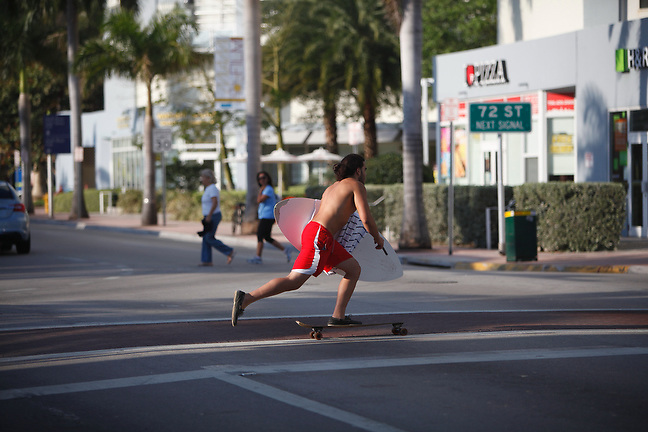 4/1/13---Miami Beach, Florida---Photo by Angel Valentin<br /> Jose Gabriel, 22, skates across Collins Avenue in Miami Beach on his way to the beach.