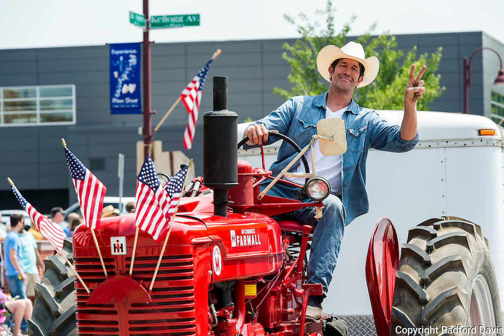 Man drives a tractor in the Fourth of July parade, Ames, Iowa