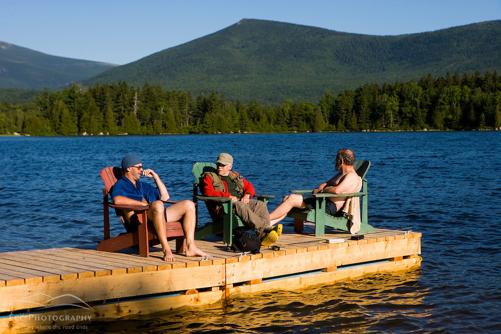 Three friends relax on the dock in Katahdin Lake in Maine's Baxter State Park.  Katahdin Lake Wilderness Camp.