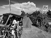 "23 JANUARY 2018 - DARAGA, ALBAY, PHILIPPINES: Evacuees in a Filipino ""tricycle taxi"" leave their village near the Mayon volcano while the volcano erupts in the background. Mayon is the most active volcano in the Philippines and its eruptions in January 2018 shut down most of Albay province and triggered the evacuation of almost 80,000 people.      PHOTO BY JACK KURTZ"