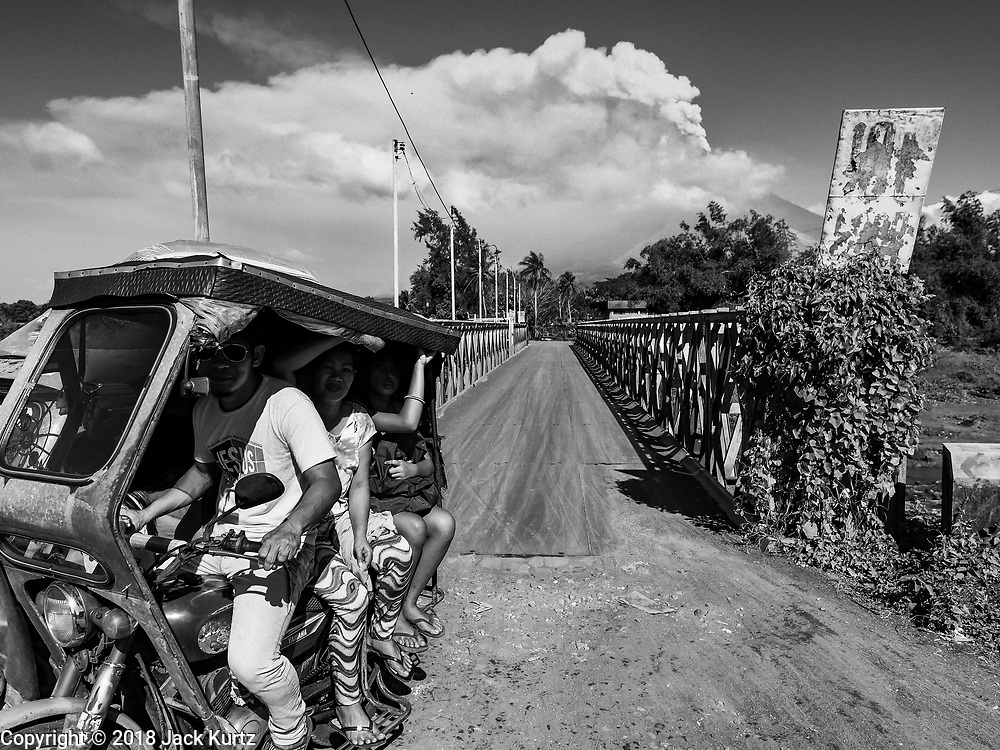 """23 JANUARY 2018 - DARAGA, ALBAY, PHILIPPINES: Evacuees in a Filipino """"tricycle taxi"""" leave their village near the Mayon volcano while the volcano erupts in the background. Mayon is the most active volcano in the Philippines and its eruptions in January 2018 shut down most of Albay province and triggered the evacuation of almost 80,000 people.      PHOTO BY JACK KURTZ"""