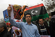 A Libyan exile burns a picture of dictator Colonel Gaddafi during protests opposite London Libyan embassy during the country's 2011 uprising. Holding up the picture of the man blamed for atrocities and for a 42-year history of oppression to his people, the flames lick around the paper, ready to engulf his image. In the background we see the pre-revolutionary flag that Libyans have adopted as their new flag after Gaddafi's downfall.