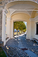Passageway leading to line of trees near the church in Loco in the Valle Onsernone in Ticino, Southern Switzerland.