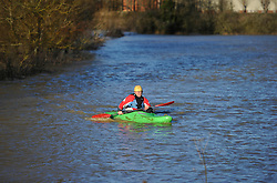 © Licensed to London News Pictures. Date 24 December 2013. Ascott Under Wychwood. Clive Taylor paddles in the flood waters of the River Evenlode. Flooding images - River Evenlode in full flood.. Photo credit : MarkHemsworth/LNP