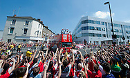 UNITED KINGDOM, London : Arsenal players wave to fans from the top of an open topped bus during their victory parade in London on May 18, 2014, following their win in the English FA Cup final football match on May 17, 2014 against Hull City. Aaron Ramsey insists Arsenal's dramatic FA Cup final victory will be the springboard for more glory now the Gunners have finally ended their trophy drought. Ramsey scored the extra-time goal that clinched a 3-2 win over Hull in Saturday's clash at Wembley, putting silverware back in the Arsenal trophy cabinet for the first time since 2005.