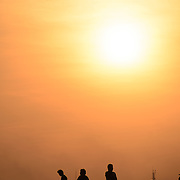 People are silhouetted against the golden setting sun in a hazy late afternoon sky along the walkway next to the Mekong River in downtown Vientiane, Laos.