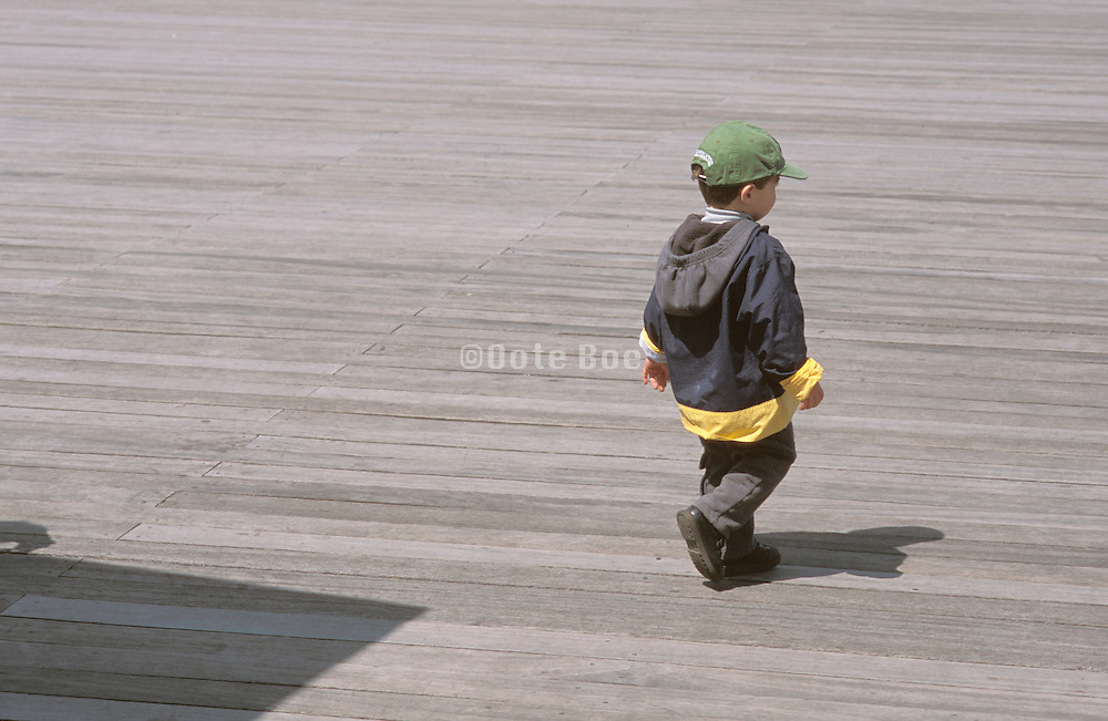 Child in a green hat walking alone on a dock