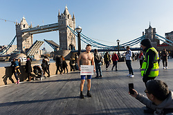 © Licensed to London News Pictures. 06/02/2020. London, UK. A student from Kowloon in Hong Kong (name not given) poses in front of Tower Bridge for his friend with a coronavirus message of support reading 'One World - One Enemy - The Coronavirus' to send to his friends back home in China and Hong Kong. Photo credit: Vickie Flores/LNP