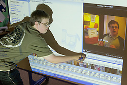 Boy with learning disability using interactive whiteboard,