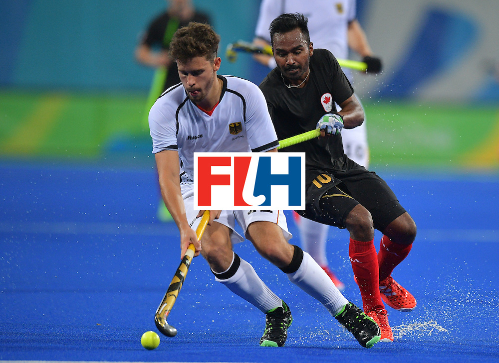 Germany's Timm Herzbruch (L) fights for the ball with Canada's Keegan Pereira during the men's field hockey Canada vs Germany match of the Rio 2016 Olympics Games at the Olympic Hockey Centre in Rio de Janeiro on August, 6 2016. / AFP / Carl DE SOUZA        (Photo credit should read CARL DE SOUZA/AFP/Getty Images)