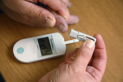 Blood glucose meter being placed on finger of diabetic patient to check sugar levels,
