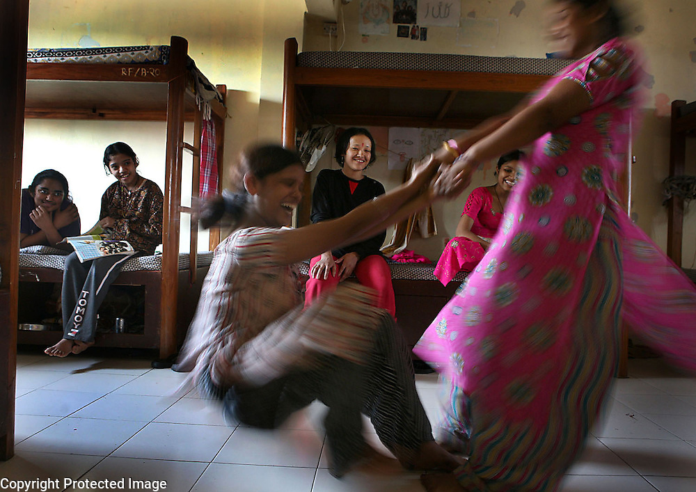 Young girls enjoy a spinning game in their hostel at the Rescue Foundation, a non-governmental organization founded to rescue young girls from brothels in and around Mumbai, India.  The Rescue Foundation houses over 50 rescued girls at a time a. Most are under the age of 18 . Many of the girls suffer from some form of post-traumatic stress syndrome.  One girl doesn't speak while another tried to commit suicide by setting herself on fire while still at a brothel.