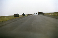 On the road to Kandahar, trucks are parked on the side road.