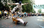 Skater doing an ollie over a man sitting in an armchair in the road, Reclaim the Streets, Camden, London, UK, 1998