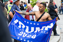 """A man displays a Trump 2020 flag as several hundred protesters in central London demand the release of """"political prisoner"""" right wing talisman Stephen Yaxley-Lennon  - also known as Tommy Robinson, who was imprisoned for contempt of court. London, August 03 2019."""