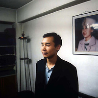 URUMQI, 5 OCOTBER 2001: the son of rebeya kadeer standing in his ofice under a protrait of his parents..rebeya kadeer used to be a successful business woman until she was jailed by Chinese for alleged subversive actions.Rebeya kadeer is famous in Xinjiang not only for her business empire but also for sponsoring poor Uighur students.. Uighur muslims in southern Xinjiang province lead very basic lifestyles and have an average monthly income of about 50 US$.. (photo by: katharina hesse/Grazia Neri)Alim Abdiryim.