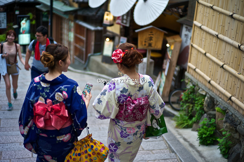 Asian women in traditional kimonos exploring the stores and shops near the Kiyomizu Temple.