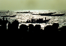 Local Mauritanian and Senegalese fishermen bring in the days harvest to local traders who wait on the beach near the capital of Nouakchott in Mauritania.  West Africa has suffered massive overfishing by foreign fishing fleets, with local small fishing boats forced to fish further and further out to sea or to concentrate their activities in sensitive coastal areas.  In the last 45 years, foreign vessels,   caught an estimated 80 percent of the fish taken from West African waters. The coastal nations took home the remaining 20 percent. And their share may get smaller..(Photo by Ami Vitale)