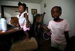 09 July 2006. New Orleans. Louisiana. <br /> Finding Faith. <br /> Faith Figueroa. A day in the life of. Faith stands at the dining room table as her sister Anfernya stands beside her. <br /> Following a ten month search for the little girl whose face appeared on the Sept 19th, 2005 cover of Newsweek magazine, Faith's mother, Miriam Figueroa has returned to town with her three children. Faith, (1 yrs), Anfernya (5yrs) and Jacquelyn (13 yrs). <br /> Credit; Charlie Varley/varleypix.com