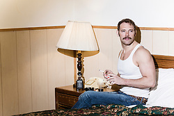 man in a white sleeveless teeshirt smoking in bed and looking off