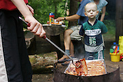 (MODEL RELEASED IMAGE).A small boy watches as his mother barbecues pork during an outing in Warsaw, Poland. (From a photographic gallery of meals in Hungry Planet: What the World Eats, p. 244).
