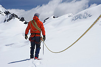 Hiker connected to safety line in snowy mountains back view
