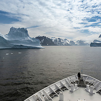 A man on the bow of the National Geographic Orion photographs icebergs in Dygalski Fjord on South Georgia Island.