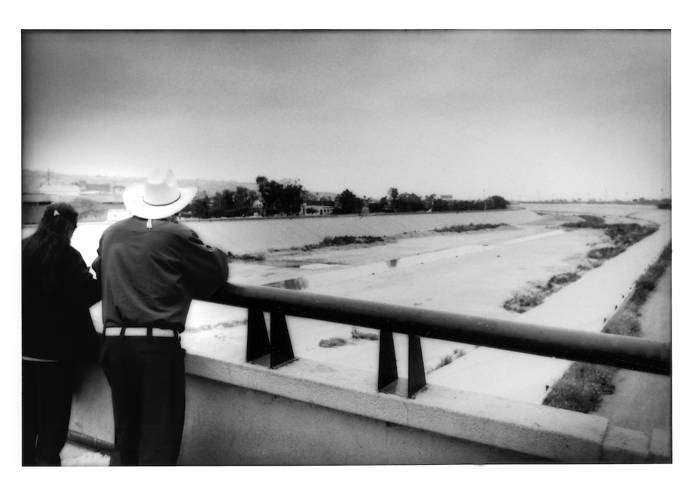 Couple looks out over Tijuana River as it approaches international border, Tijuana, Baja California, Mexico.    The river will cross over to the American side at the beginning of the bend to the left.  The Tijuana River is predominantly a trough of untreated sewage at this point.