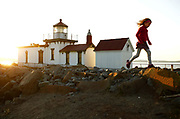 A child rock hops near the West Point Lighthouse at Discovery Park. (Erika Schultz / The Seattle Times)