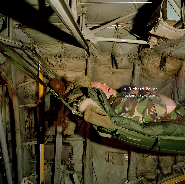 Corporal Chris Ward, one of the photographers belonging to the elite 'Red Arrows', Britain's prestigious Royal Air Force aerobatic team, reads a novel while wrapped up in sleeping bag and hammock aboard a C-130 Hercules transport aircraft during a two-day journey from RAF Scampton to RAF Akrotiri, Cyprus. Corporal Ward has established for himself a comfortable nest in the rear section at the loading ramp. The interior is basic with sharp corners but the walls are padded.  Ward wears a heavy camouflaged coat to counteract the cold and ear-plugs from the droning engines. The Red Arrows pilots fly their Hawk jet aircraft to air shows but on long journeys requiring the support of ground crew borrow RAF transporters that fly behind the main airborne squadron shipping 10 tons of spares and personal effects for their six-week winter training stay.. .