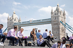 © Licensed to London News Pictures. 26/07/2018. London, UK. Office workers in London Bridge have their lunch outside during hot weather. Today is predicted to be the hottest day of the year, with temperatures in the capital set to rise up to 35 degrees, as the UK experiences a prolonged heatwave. Photo credit : Tom Nicholson/LNP