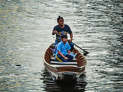 27 SEPTEMBER 2016 - BANGKOK, THAILAND:  A woman uses her canoe to take her child to school in the khlong (canal) at the floating market in Damnoen Saduak, Thailand. The market is famous because vendors cruise the canals around the market selling produce and tourist curios. It is one of the best known tourist attractions in Samut Songkhram province.     PHOTO BY JACK KURTZ