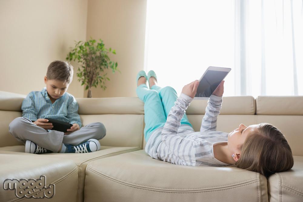 Siblings using technologies on sofa at home