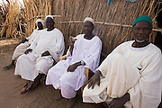 Four Sudanese gentlemen sit in the shade of the 4 sq km Abu Shouk refugee camp which is (disputedly) home to 38,000 displaced persons and families on the outskirts of the front-line town of Al Fasher (also spelled, Al-Fashir) in north Darfur. .