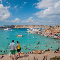 People swimming at Comino beach Gozo, Malta.