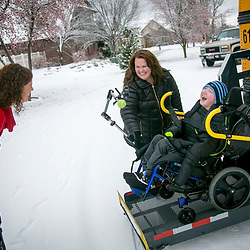 Alissa Aldrich (left) laughs with son Lucas (right, age 9) as he is helped off a school bus by Nichole Paul with Cascade Student Transportation. Alissa Aldrich takes care of her 9-year-old son, Lucas, full time. Lucas has a life-limiting neuro disorder called Lissencephaly. Tuesday December, 06, 2016.