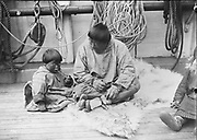 Native American child and man sitting on deck of a ship, possibly the Revenue Cutter 'Bear' during a relief voyage to rescue whalers off the Alaska coast, 1897. Man is showing child how to smoke a pipe. Dr Samuel J. Call (1858-1909)