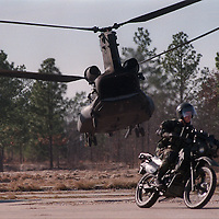 A member of the 75th Ranger Regiment rides away on a motorcycle as the CH47 Chinook from which it came flies away during a demonstration at Camp Mackall.<br /> ***POSSIBLE LEAD PHOTO****