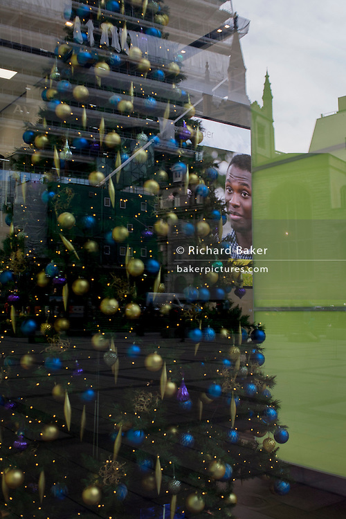 A face looks out from a screen in the Aviva office foyer during a rolling Christmas video for the insurance corporate, on 9th December 2016, in the City of London.