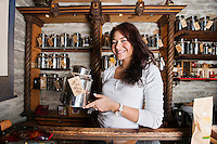 Portrait of smiling salesperson displaying tea container in store