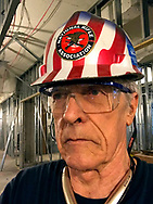 A man with a hard hat wearing safety glasses.