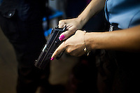 Elaine Soares Concei&ccedil;&aacute;o, right, checks her gun as she prepares for her shift, in Complexo do Caju, Rio de Janeiro, Brazil, on Friday May 10, 2013.<br /> <br /> In the early hours of Sunday, March 3, 2013, about 1,400 Brazilian security forces occupied 13 communities during a joint public security operation to install a Pacifying Police Unit (UPP) in two Rio de Janeiro favelas, Complexo do Caju and Barreira do Vasco. Elite police units backed by armored military vehicles and helicopters invaded the neighborhood in an on-going policing program aimed to drive violent and heavily armed drug gangs out of Rio's poor communities, where the traffickers have ruled for decades. For the community of Caju, that is ADA (Amigos de Amigos) and CV (Comando Vermelho).